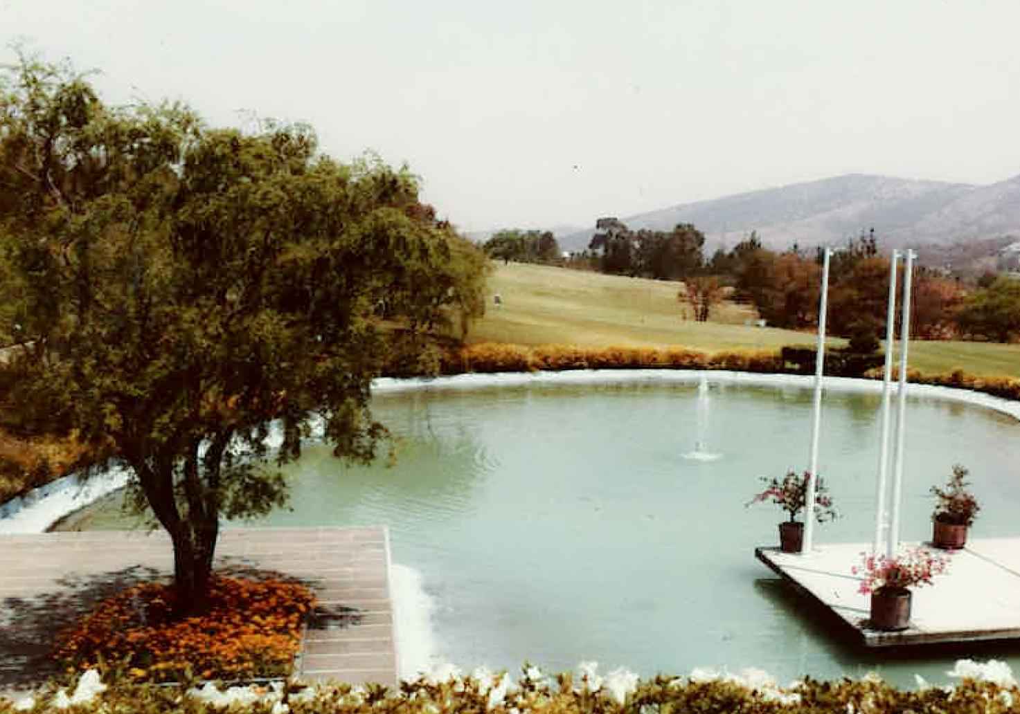 Lago con fuente en el centro y al fondo las vistas del campo de Golf