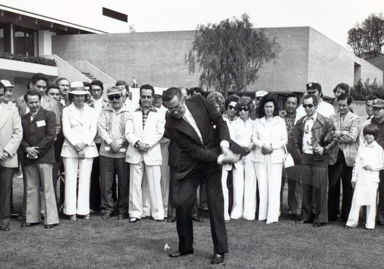 Personas admirando el swing de un golfista