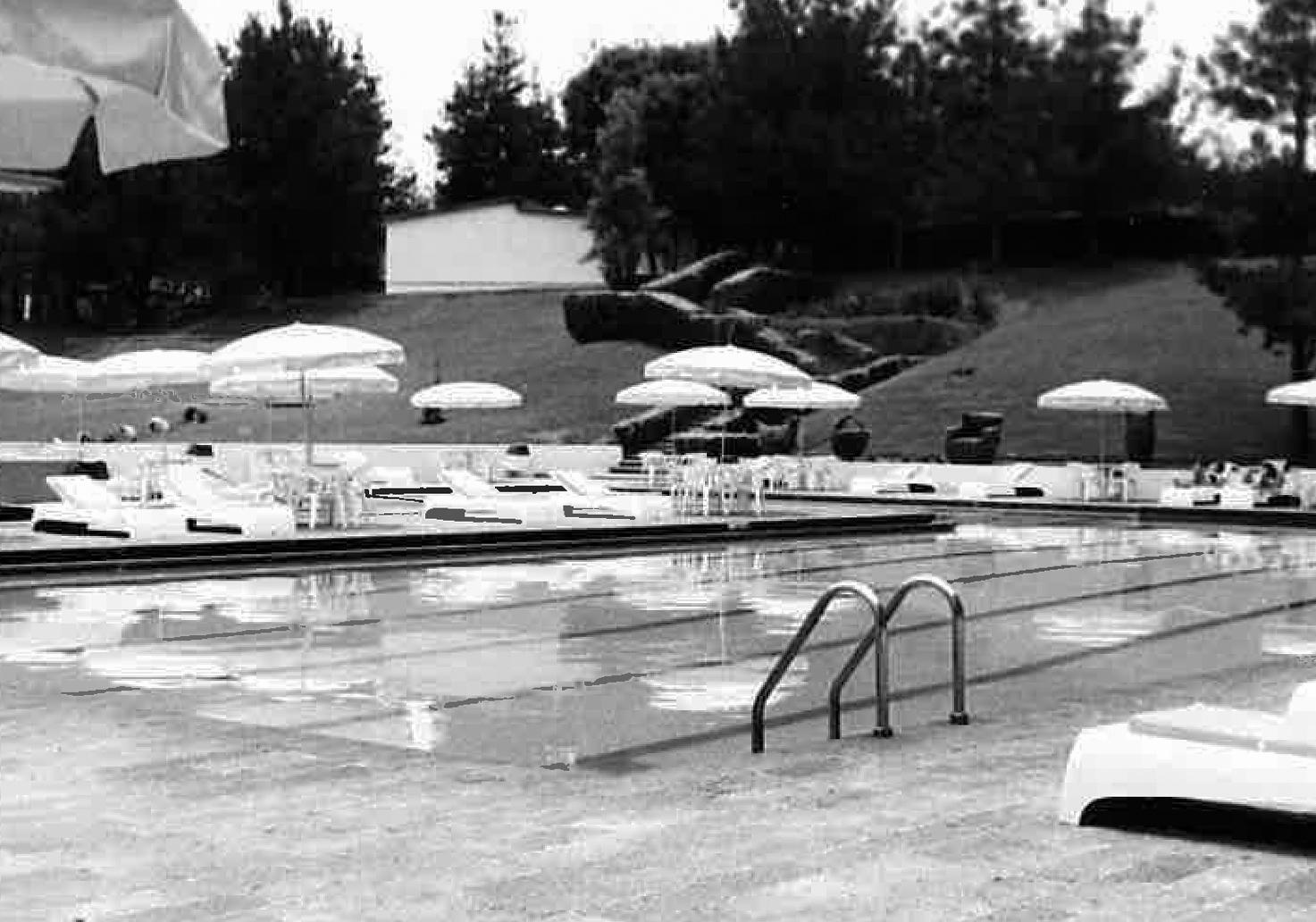 Foto en blanco y negro con las piscinas exteriores y árboles al fondo