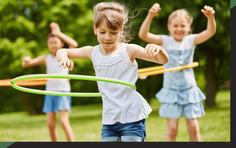 Niñas pequeñas bailando el hula hop